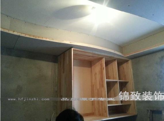 九厘板做背板,用波音软片饰面,实木线条收口.